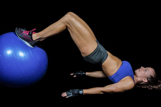 Side view of woman exercising with ball against black background