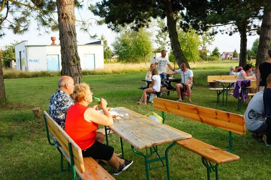 SIANOZETY, POLAND - JULY 22, 2015: People sitting on benches by wooden tables on a barbecue event