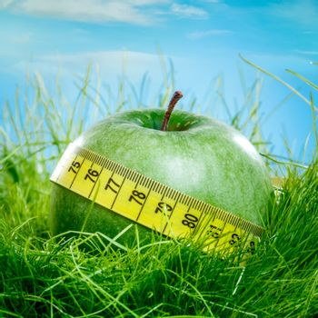 Green apple and measuring tape on the green grass.