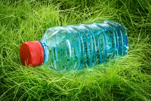 Bottle of water on the green grass