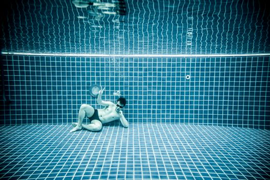 Man lies under water in a swimming pool