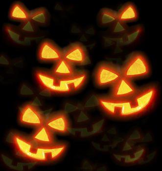 Lots of pumpkins lit brightly against a black