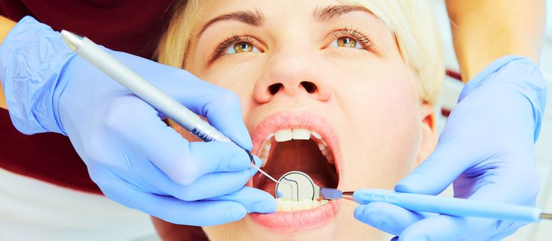 Close-up of a pretty patient with her mouth open in dental clinic