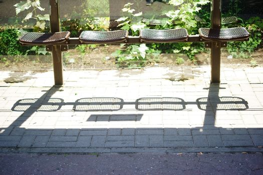 The seats of a bus stop throwing abstract shadows.