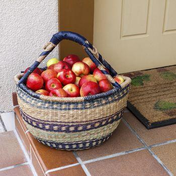 Fresh red apples in a basket standing at doorway