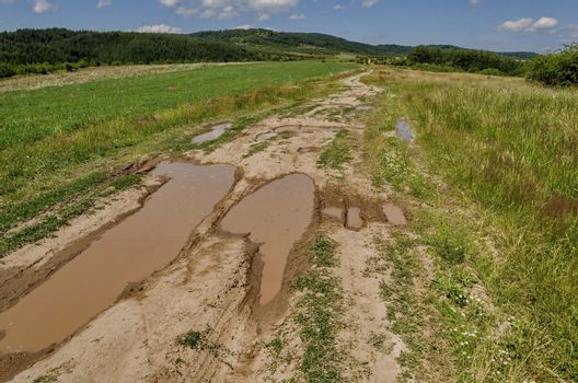 Background of sky, clouds, field,  road with puddle after flood rain and forest, Plana mountain, Bulgaria