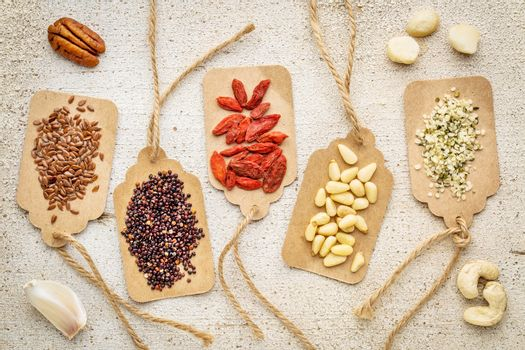a vriety of superfood (nuts, berries, grain, seed) on paper price tags against grunge barn wood background