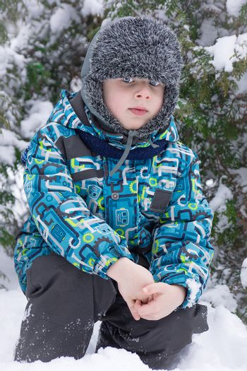 A boy sits near a Christmas tree in the snow