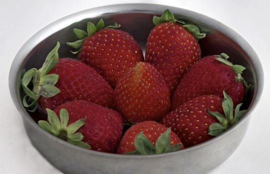 Strawberries with leaves on the bowl