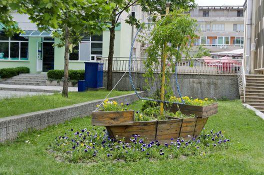 Garden popular with grass and  pansy (Viola altaica) flower in original flowerpot - wooden boat