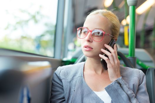 Blonde caucasian business woman talking on cell phone, traveling by bus. Public transport and commuting to work.