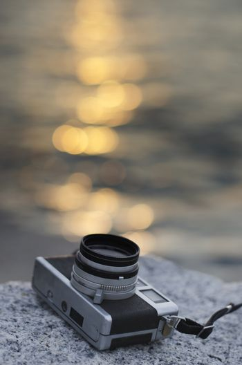 Relax with vintage camera beside sea with sunset reflected bokeh background