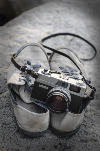 Vintage film camera on shoes with texture overlay background