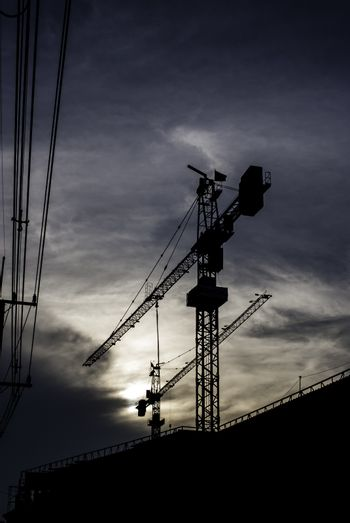 Silhouette of crane on building with sunset sky background