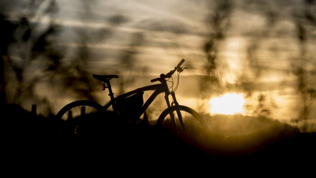 Silhouette of mountain bike with sunset light