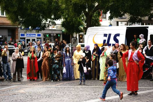 Mainz, Germany - September 25, 2015: A Kurdish woman holding a child in her arms and presented a colorful costume at an event organized by the Intercultural Weeks on September 25, 2015 in Mainz.