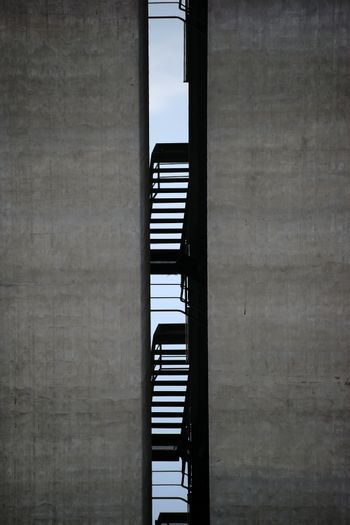 A staircase between two distinctive industrial buildings made of concrete.