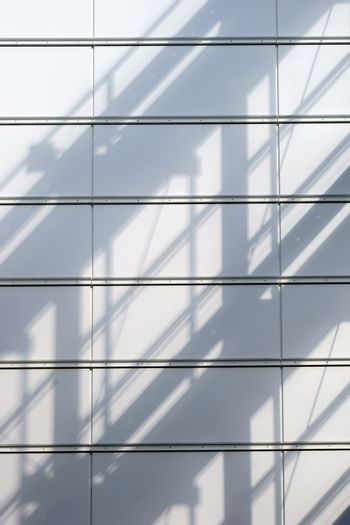 An abstract shadow of a railing and roof structure on a metal cladding.