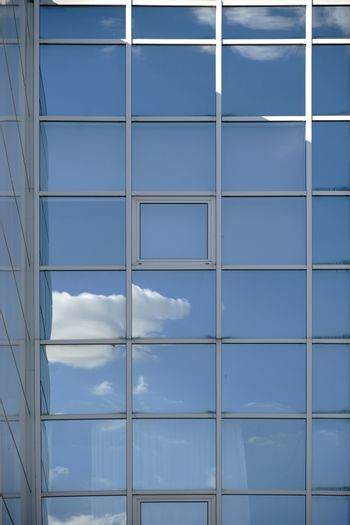 A white cloud and reflections in the window of a modern facade.