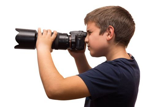 the photograph depicts a young boy with a camera