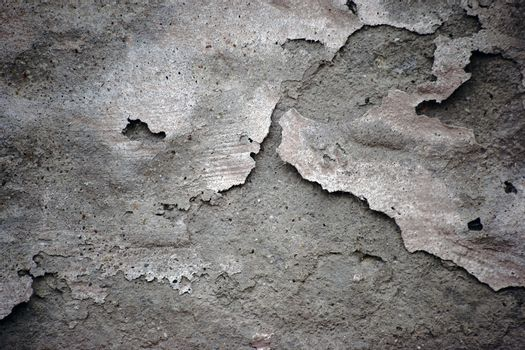 A flaking plaster layer on the surface of a concrete wall can be used as background.