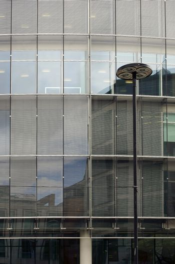 The facade of a modern office building with blinds in the windows and a lantern in front of the building.