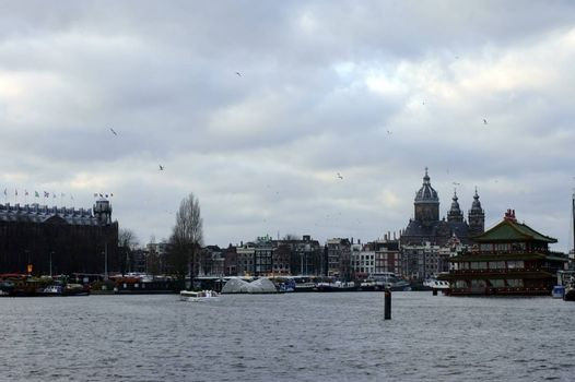 Amsterdam, Netherlands - December 31, 2014: The views over the open water with anchored ships, the floating Chinese restaurant and the St. Nicholas Church in the background on December 31, 2014 in Amsterdam.