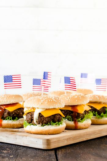 Mini beef burgers with American flag on wooden board,selective focus and blank space
