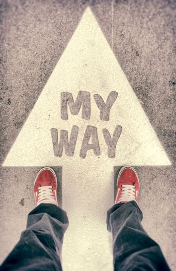 Brand new red shoes from above standing on myway sign