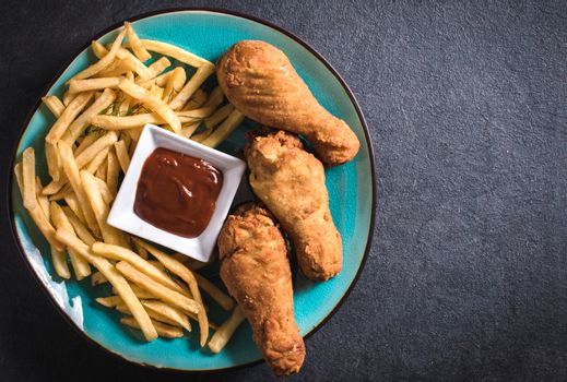 French fries and fried chicken legs on dark background with blank space