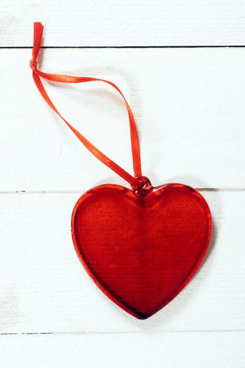 Red and white heart shape object on wooden background