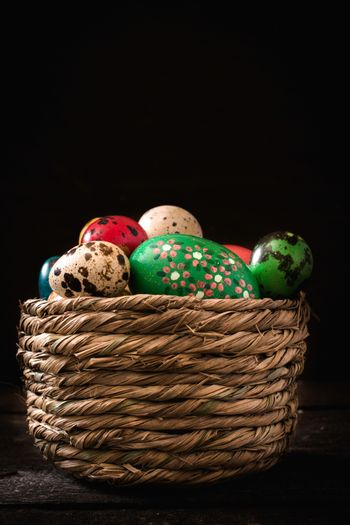 Colorful Easter eggs in the basket on wooden background