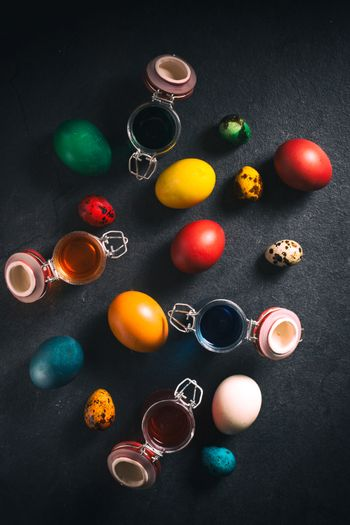 Colorful Easter eggs from above on dark background