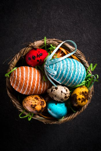 Easter eggs in wooden basket from above,selective focus
