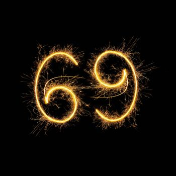 Number 69 in sparkling digits isolated on black background. Symbol of sexual position 69.