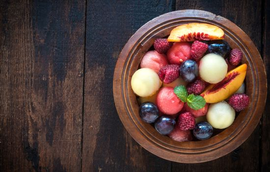 Fruits salad served on wooden background with blank space