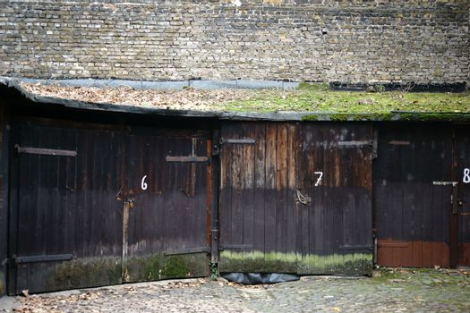 Several old garages in the courtyard of an apartment house with wooden board doors covered with moss.