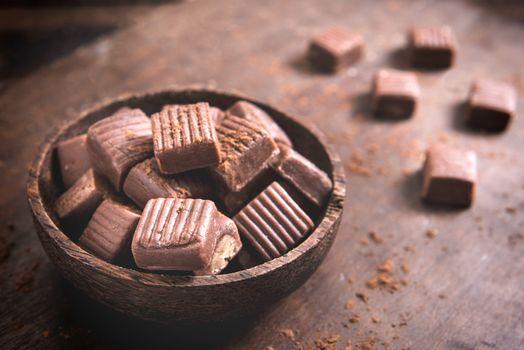 Chocolate handmade caramel bonbons in wooden bowl,selective focus
