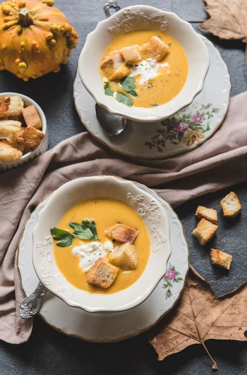 Served homemade pumpkin soups with milk cream and croutons, from above