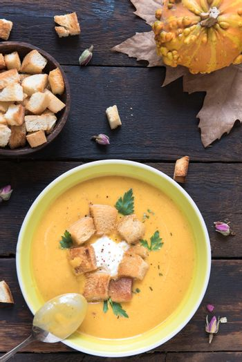 Homemade pumpkin soup with milk cream and croutons bread in the plate, from above