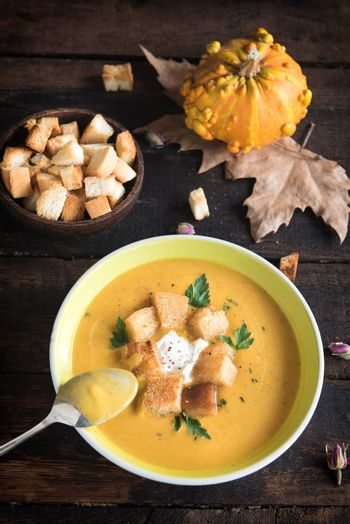 Served homemade pumpkin soup with milk cream and croutons bread in plate, selective focus