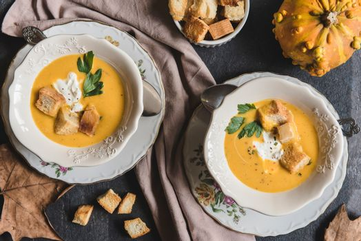 Served homemade pumpkin soup with milk cream and croutons bread in bowl, selective focus