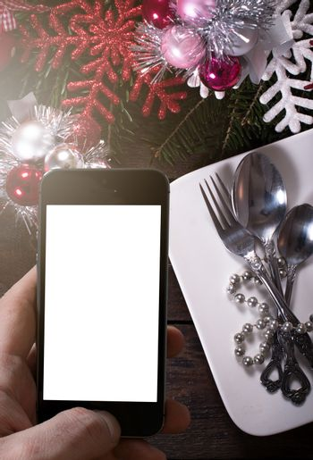 Wooden background with blank screen on phone and Christmas decoraton