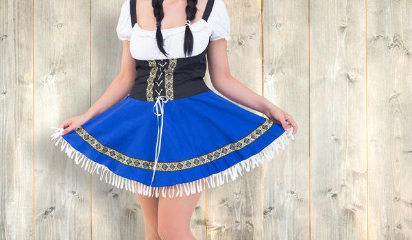 Oktoberfest girl spreading her skirt against pale wooden planks