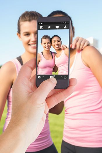 Female hand holding a smartphone against two smiling women wearing pink for breast cancer