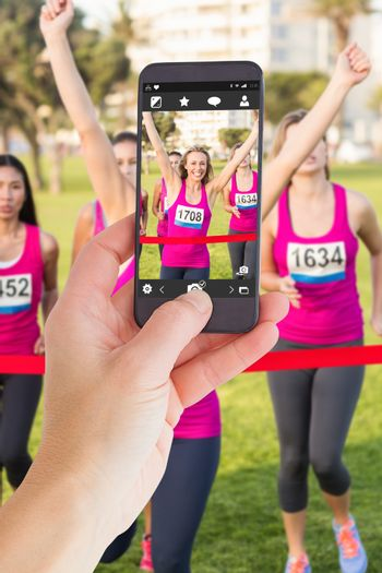 Female hand holding a smartphone against cheering blonde winning breast cancer marathon