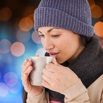 Composite image of smiling brunette drinking hot beverage