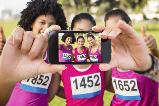 Hand holding smartphone showing against three smiling runners supporting breast cancer marathon