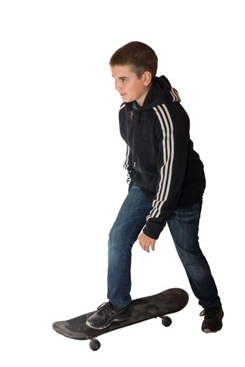 The picture shows a boy riding on a skateboard.