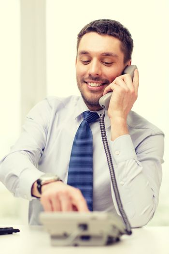 smiling businessman with telephone dialing number